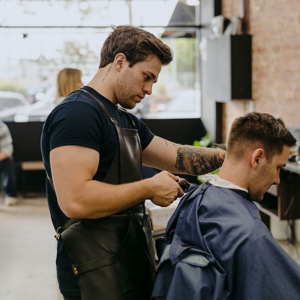 Man giving a hair cut in a barber shop in Lilydale
